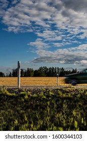 Two mile / kilometer posts on both sides of a summer asphalt road under a cloudy blue sky and a golden wheat field with a forest in the background and a motion blur car speeding through the posts