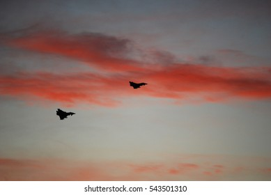 Two military aircraft in the sky, pink clouds