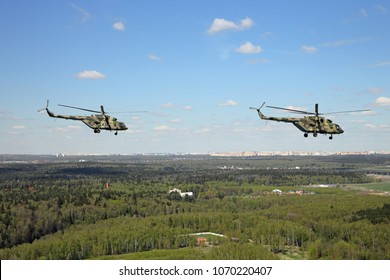 Two military helicopters in the sky over the forest