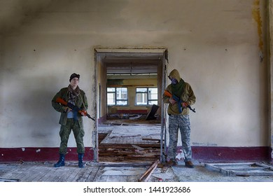 two military mercenaries in masks and with weapons guard something inside an abandoned building