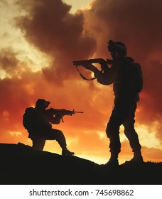 Two military silhouettes on sunset sky background