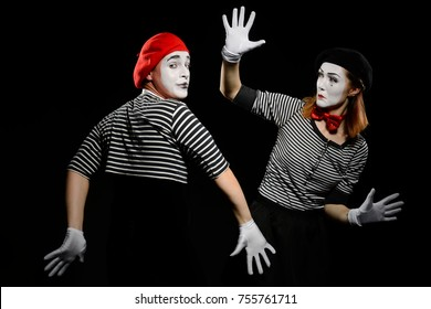 Two mimes and invisible wall. Pantomime show at circus, performed by man and woman as mime artists. Illusion concept.