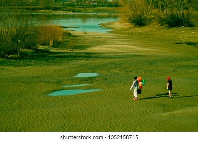 two mims in striped clothes go away a sandy wasteland with balloons and suitcase past the river and puddles