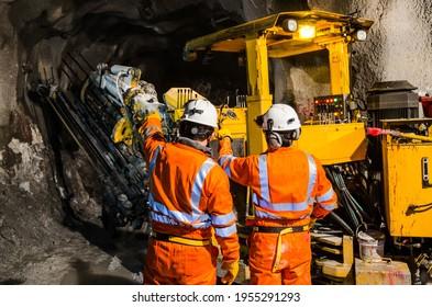 Zwei Mineningenieure mit Schutzhelmen stehen und reden auf einer riesigen Bohrmaschine, sprechen und beobachten an der Grabstelle. Rückansicht.