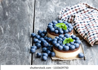 Two mini  chocolate cheesecake with fresh blueberry on wooden table