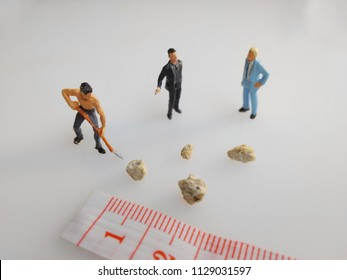 two mini figure businessman discussion about kidney stone and worker try moving it