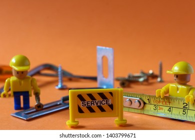 Two mini figure toys in construction worker uniforms working with tools with table captioned SERVICE in front of them. Editorial image, macro photography, studio shot, close up photo.