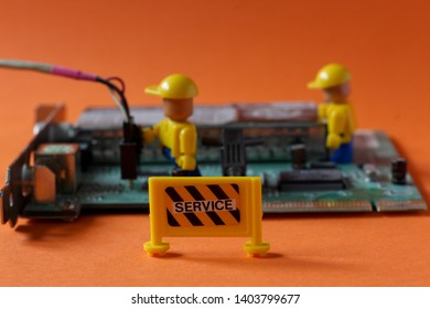 Two mini figures in engineer uniforms with helmets working on servicing hi tech peace of computer technology. Editorial image, close up photo, studio shot, macro photography, isolated on orange