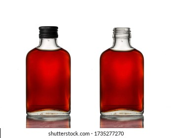 Two mini glass bottles with brown beverage, one with a black cap and another one open.
