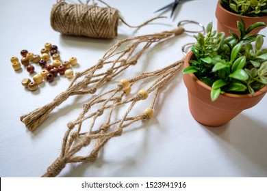 Two mini jute twine plant hangers are being displayed by a bolt of jute twine, some beads, and the faux plants in pots that will hang in the macrame.