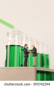 Two Miniature Businessmen Handshaking On Test Tube Rack With Green Chemical In Background