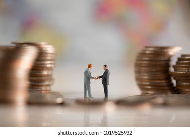 two miniature businessmen make an agreement in the group of the coin stack with background is world map illustrate financial, business, agreement concept