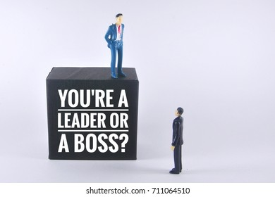 Two miniature bussiness people with blackbox written you're leader or a boss. Leader and business concept