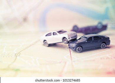 Two Miniature cars accident crash on road, insurance case and broken toys auto car on on Bangkok city map background. Vehicle insurance is insurance for cars, trucks, motorcycles, other road vehicles.