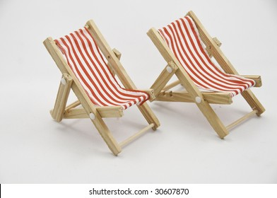 Two miniature chairs on a white background.