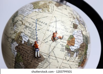 Two miniature climbers clinging to the globe.
