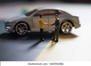 Two miniature men shake hands in front of a car. Used or new car sales. Buying or selling automobiles. Good deals on brand new wheels. People make a business agreement about a vehicle.
