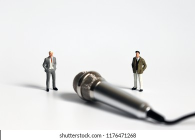 Two miniature men in suits and a silver microphone.