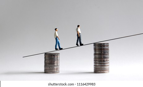 Two miniature men walking on two piles of coins.