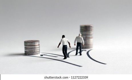 Two miniature men walking toward a stack of coins of different heights.