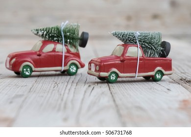 Two miniature red car with fir tree on wooden background. Shallow DOF