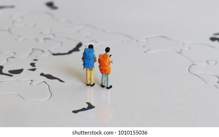 Two miniature tourists standing on a world map with a rucksack.