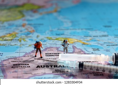 Two miniature travelers standing on a world map and two disposable syringes.