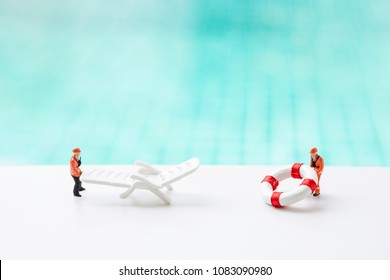 Two miniature worker moving plastic white beach chair and life buoy at the swimming pool edge over blurred blue water, summer and safety concept at poolside, outdoor day light