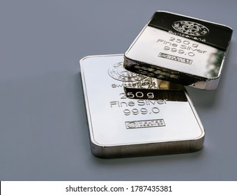 Two minted silver bars weighing 250 grams each on a gray background. Selective focus.