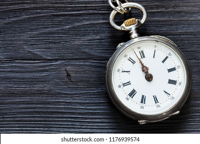 two minutes to twelve o'clock on retro pocket watch on black wooden background