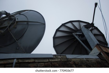 Two mirrored satellite antennas on the roof of an industrial house