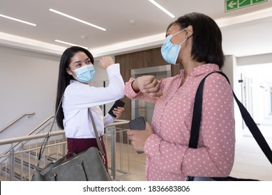 Two mixed race female colleagues working in a modern office wearing face masks greeting each other by touching elbows. Hygiene and social distancing in workplace during Coronavirus Covid 19 pandemic.