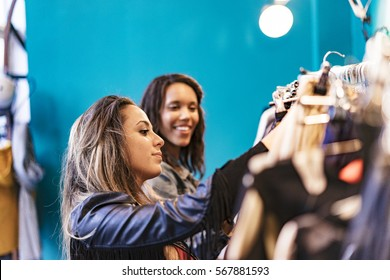 two mixed race female friends buying clothes in a store and having fun