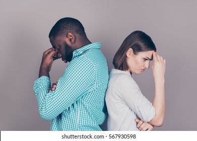 two mixed race people having headaches and stress.  Handsome afro american guy standing together with  his  beautiful caucasian girl.