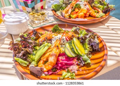 Two  mixed salads on a white wooden table with stripes caused by a sunshade in a beach bar. The healthy salad on a round plate has shrimps, avocado, cumcumber, lettuce, onion, mango and broccoli.