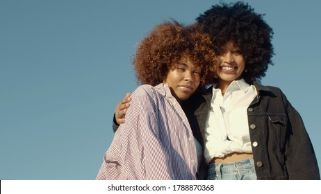 Two mixed-race black woman hugs Outdoor portrait of two mixed-race woman with huge afro hair
