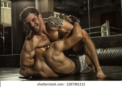 Two MMA fighters grappling on training in gym. Muscular sportsman with aggressive look looking at camera, sitting on chest of rival and choking him with hand, opponent lying in floor and resisting.