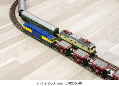 Two model trains on wooden floor, game for kids