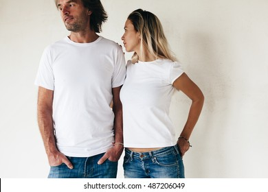 Two models man and woman wearing blanc t-shirt posing against white wall, toned photo, front tshirt mockup for couple
