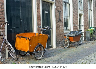 Two modern Dutch transport bikes in front of medieval homes.  Bikes with carts are nowadays used by urban parents to bike their children to school.