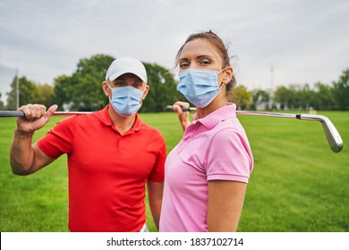 Two modern golfers in disposable face masks and polo shirts standing on the golf course