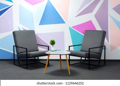 Two modern grey chair against a white wall with colored geometrical figure.Book laying on little table, green plant.Light of lamps.Copy space