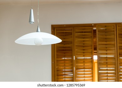 Two modern lamps in front of the window with shutters