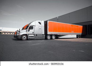 Two modern professional commercial semi trucks in gray and orange with dry van trailers are standing in the dock on territory of the transport warehouses for loading or unloading of commercial cargo