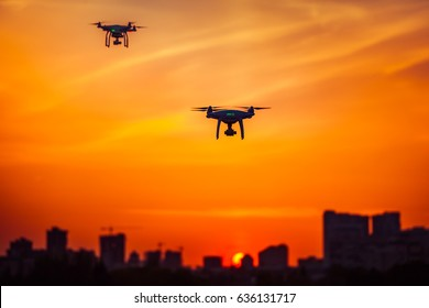 Two modern Remote Control Air Drones Fly with action cameras in dramatic orange sunset sky. Cityscape silhouette in the background. Modern technologies. Kiev, Ukraine. Travel, hobby, inspiration