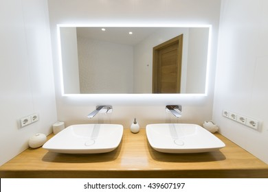 Two modern sink in the bathroom, and big mirror with blue mask