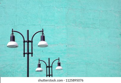 Two modern street lamps on empty building facade in turquoise tone with copy space.