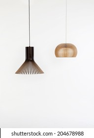two modern wooden chandeliers on white backgrounds