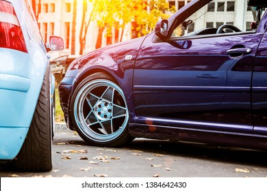 Two modified low cars in purple candy and light blue color. Stance custom cars with a forged polished wheels parked on a street at sunny day. Tuned automobiles