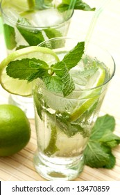 Two mojito cocktails with lime, mint leaves and ice on wooden placemat background